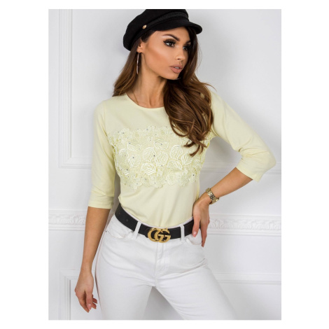 Yellow blouse with a floral application